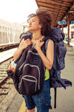 Beautiful tourist traveler standing with huge luggage. At the railway station near the tracks Royalty Free Stock Photos