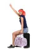 A beautiful tourist woman with baggage showing sign isolated on Stock Images