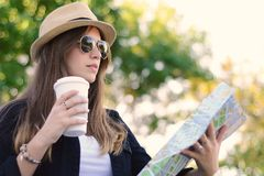 Young tourist woman with coffee looking at the map. Royalty Free Stock Images