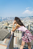 Beautiful tourist woman looking to Genova port from balcony over the city Stock Photography