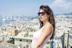 Beautiful tourist woman looking to Genova port from balcony over the city Royalty Free Stock Images