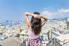 Beautiful tourist woman looking to Genova port from balcony over the city Stock Photo