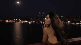 Beautiful tourist woman in night city. Freedom, in love, dating concept. Young romantic tourist woman standing on bridge against ligths of night city background stock video