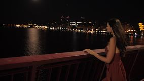 Beautiful tourist woman in night city. Freedom, travel, lifestyle, dating concept.Young romantic tourist woman standing and then walking over the bridge against stock video footage