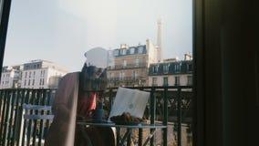 Beautiful tourist woman using laptop sitting at idyllic Paris apartment balcony, view through window glass reflection. stock video