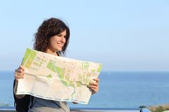 Beautiful tourist woman on vacation with a city map. With the sea and sky in the background Royalty Free Stock Photography