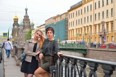 Beautiful tourists rest at the gate of the Griboyedov Canal emba Royalty Free Stock Images