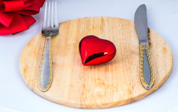 Beautiful toy heart lies on a chopping board Royalty Free Stock Image