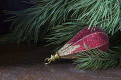 Beautiful toy rests upon table under fir tree. On dark background Royalty Free Stock Image