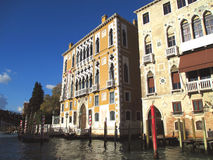Beautiful traditional architecture with colorful mooring poles against vivid blue sky of Venice Stock Images