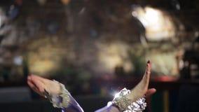 Beautiful traditional female dancer dances belly dancing in restaurant. Hot brunette woman ethnic dances performing belly-dance in romantic atmosphere. Dark stock video footage