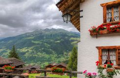Swiss house in the alps. Beautiful traditional house in the alpine village Grimentz, Switzerland, in the canton Valais, municipality Anniviers, with geranium royalty free stock image