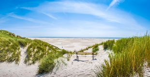 Beautiful tranquil dune landscape and long beach at North Sea, Germany. Beautiful tranquil dune landscape with idyllic bench overlooking the German North Sea and royalty free stock images