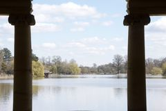 Lake seen between silhoutted columns stock photo