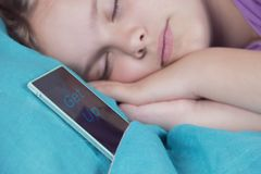 A beautiful tranquil girl sleeps on the bed, next to her phone, soon the alarm will ring. royalty free stock image