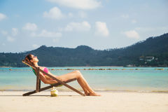 Beautiful, tranquil lady tanning while lying in the lounge with a fruit cocktail on the beach Stock Image