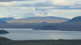 Beautiful tranquil lake and huge snow-capped mountain in horizon, picturesque clouds. Are over fairytale landscape of Iceland stock footage
