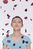 Beautiful tranquil young woman looking up with eyes closed with rose petals flying around her Royalty Free Stock Photos