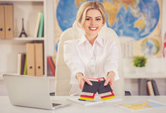 Beautiful travel agent. Beautiful female travel agent is offering tickets and smiling while sitting at office Stock Images