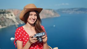 Beautiful travel woman in hat posing holding camera at sea landscape background at sunny summer day. Portrait of female fashionable tourist relaxing outdoor stock video