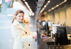 Beautiful traveler doing check-in in the airport Stock Photo
