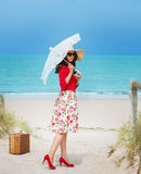 Beautiful  traveler. Beautiful lady in red traveler in retro style dress  on the beach Royalty Free Stock Photography