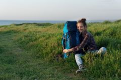 Beautiful traveler woman hugging her backpack in grass and smiling Royalty Free Stock Images
