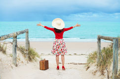 Beautiful  traveler. Beautiful woman traveler in retro style dress  on the beach Royalty Free Stock Photo