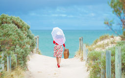 Beautiful  traveler. Beautiful woman traveler in retro style dress  on the beach. Local focus on the woman Stock Image