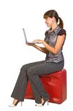 Beautiful  traveller. Attractive businesswoman sitting on suitcase with laptop on her hands Royalty Free Stock Image
