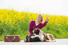 Beautiful traveller girl. Girl with a dog hitchhike Stock Image