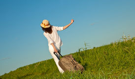 Beautiful traveller walking with a suitcase Royalty Free Stock Image