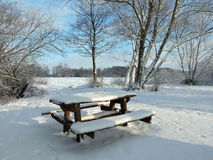Beautiful trees and resting place near river in winter. Beautiful snowy trees, bench and table  in winter near river Atmata, Lithuania Royalty Free Stock Images
