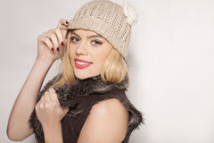 Beautiful trendy blond in winter fashion. Beautiful trendy blond woman in winter fashion wearing a fur jacket and warm knitted cap standing sideways smiling at Royalty Free Stock Images