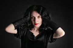 Beautiful trendy girl with fashionable makeup wearing a black dress Royalty Free Stock Image