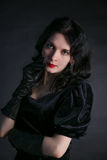 Beautiful trendy girl with fashionable makeup wearing a black dress Stock Photos