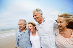 Beautiful trendy seniors walking on the beacdh Stock Photography