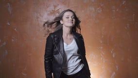 Beautiful trendy woman dancing over orange background. Beautiful brunette woman wearing leather jacket posing in studio stock footage