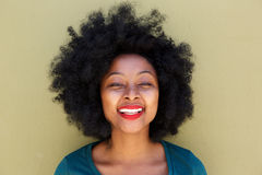 Beautiful trendy young woman smiling by wall Royalty Free Stock Photography