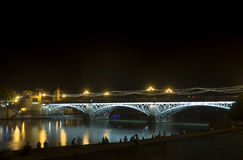 Beautiful Triana bridge next to the Guadalquivir river on its way through the city of Seville, Andalusia. Views of the most famous bridges in the city of Seville stock photography