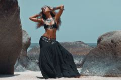 Beautiful tribal woman on the beach. Belly dance tribal fusion young woman with silver and gold ethnical accessories Royalty Free Stock Photo