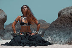 Beautiful tribal woman on the beach. Belly dancer tribal fusion young woman with silver and gold ethnical accessories Stock Photos