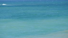 Beautiful tricolor sea with different shades of turquoise blue and dark green with waves and white foam on it