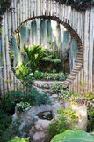 Beautiful tropical asia style with green color garden idea with circle bamboo wall decoration and small lake Stock Image