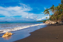 Beautiful tropical beach with black sand. Summer vacation concep. T Stock Photography