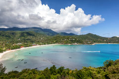 Beautiful tropical beach with blue water and green hills, top vi Stock Photos
