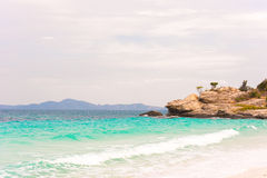 Beautiful tropical beach with clear turquoise water and cliffs, Pattaya, Thailand. Ocean waves on the beach. Copy space. Royalty Free Stock Images