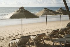 Beautiful tropical beach with deck chairs and parasol Stock Photo