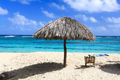 Beautiful tropical  beach Maguana, Cuba. Umbrella and wooden chair on beautiful tropical beach  Maguana, Guantanamo province, Cuba Stock Image