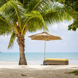Beautiful tropical beach, palm tree, sea water, umbrella and sunbed on a sunny day. Thailand Royalty Free Stock Images